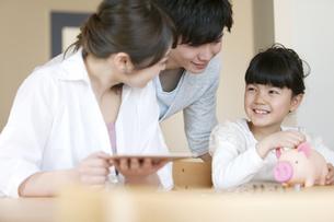 貯金箱と家族の写真素材 [FYI01317854]