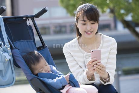 ベビーカーで寝てる赤ちゃんと女性の写真素材 [FYI01317870]