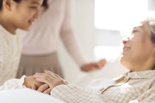 入院している祖母と手を取り合う孫娘の写真素材 [FYI01317934]