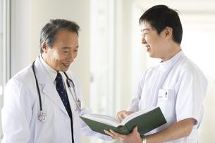 書籍を見て話をする男性医師と看護師の写真素材 [FYI01317966]