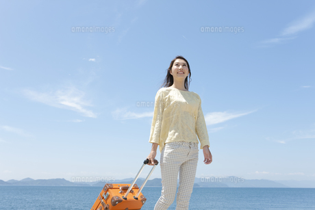スーツケースを引いて歩く女性の写真素材 [FYI01317973]