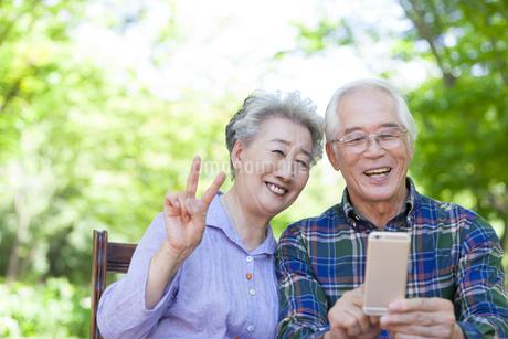 スマートフォンを持つシニア夫婦の写真素材 [FYI01317990]