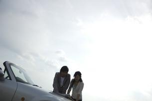 ボンネットに広げた地図を見るカップルの写真素材 [FYI01318011]