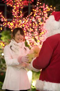 サンタにプレゼントをもらってうれしそうな女性の写真素材 [FYI01318015]