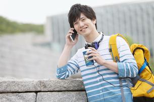 スマートフォンで通話する男子学生の写真素材 [FYI01318092]