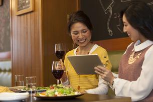タブレットPCを見ながら会話する女性2人の写真素材 [FYI01318157]