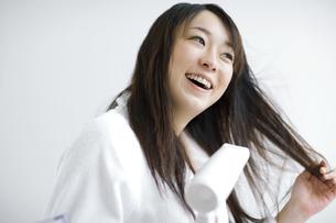 ドライヤーで髪を乾かしている女性の写真素材 [FYI01318405]