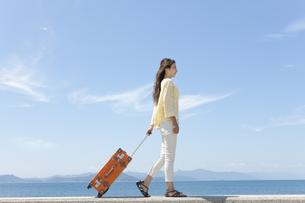 スーツケースを引いて歩く女性の写真素材 [FYI01318438]