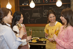 グラスを持って会話する女性4人の写真素材 [FYI01318472]