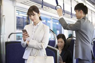 通勤電車に乗るビジネスマンとビジネスウーマンの写真素材 [FYI01318648]