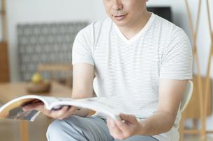 雑誌を読む男性の写真素材 [FYI01318858]