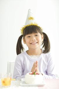 ケーキを前にうれしそうな女の子の写真素材 [FYI01318859]
