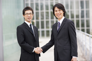 笑顔で握手するビジネスマン2人の写真素材 [FYI01318963]