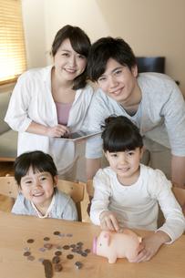 貯金箱と家族の写真素材 [FYI01319030]