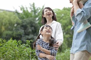 公園を歩く4人家族の写真素材 [FYI01319052]