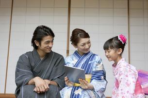 タブレットPCを見る浴衣姿の日本人家族の写真素材 [FYI01319173]