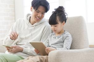 タブレットPCを見ている父娘の写真素材 [FYI01319197]