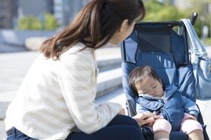 ベビーカーで寝てる赤ちゃんと母親の写真素材 [FYI01319201]