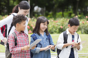 タブレットPCを見る小学生と先生の写真素材 [FYI01319220]