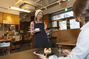 コーヒーを運ぶカフェ店員の写真素材 [FYI01319229]