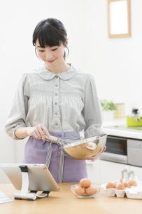 タブレットPCを見ながら調理する女性の写真素材 [FYI01319454]