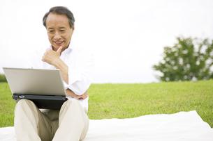 パソコンを見て考えているシニア男性の写真素材 [FYI01319530]