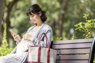 公園のベンチでスマートフォンを見る妊婦の女性の写真素材 [FYI01319569]