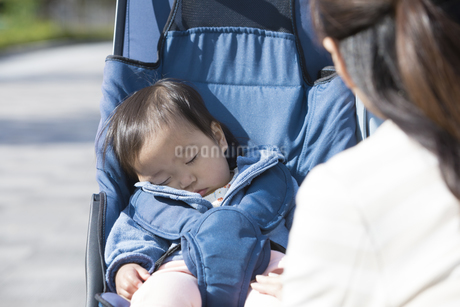 ベビーカーで寝てる赤ちゃんと女性の写真素材 [FYI01319643]