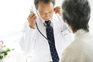 聴診器を耳にかける男性医師の写真素材 [FYI01319692]