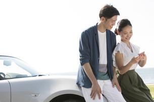 スマートフォンを見ている笑顔のカップルの写真素材 [FYI01319698]
