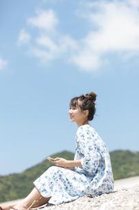 砂浜に座ってスマートフォンを持っている女性の写真素材 [FYI01319774]