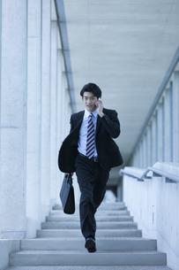 電話しながら走るビジネスマンの写真素材 [FYI01319779]