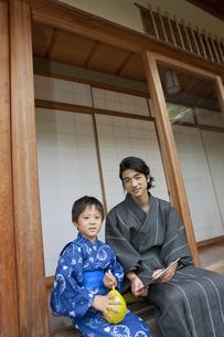 縁側の座る浴衣姿の日本人親子の写真素材 [FYI01320017]