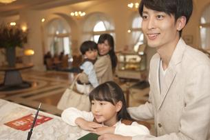 ホテルのフロント前にいる4人家族の写真素材 [FYI01320221]