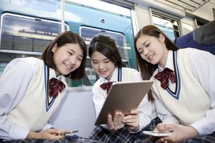 電車でタブレットPCを見ている女子高生の写真素材 [FYI01320292]