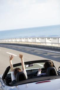 オープンカーに乗るカップルの後姿の写真素材 [FYI01320340]