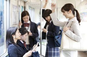 電車移動しているビジネスウーマンと女子高生の写真素材 [FYI01320710]