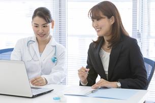 打ち合わせをする女医とビジネスウーマンの写真素材 [FYI01320770]