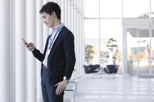 スマートフォンを見ているビジネスマンの写真素材 [FYI01320819]