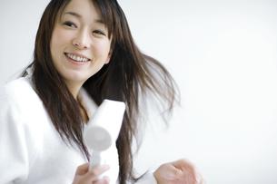 ドライヤーで髪を乾かしている女性の写真素材 [FYI01320838]
