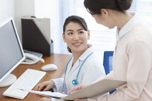 カルテを見ながら話す女医と看護師の写真素材 [FYI01321008]