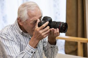 カメラを持つシニア男性の写真素材 [FYI01321022]