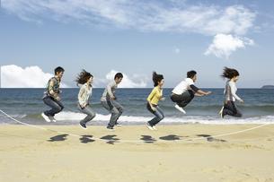 砂浜で大縄跳びをする若者6人の写真素材 [FYI01321034]