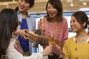 プレゼントを渡してお祝いする女性4人の写真素材 [FYI01321038]