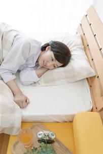 ベッドで横になる中高年女性の写真素材 [FYI01321070]