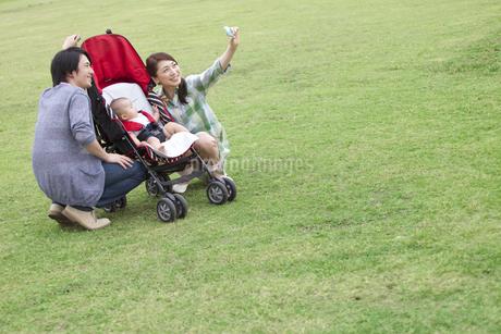 スマートフォンで写真を撮る3人家族の写真素材 [FYI01321107]