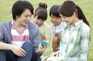 スマートフォンを見ている4人家族の写真素材 [FYI01321285]