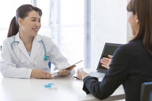 打ち合わせをする女医とビジネスウーマンの写真素材 [FYI01321561]