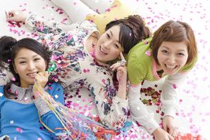 散らばった紙吹雪の上に寝転ぶ女性3人の写真素材 [FYI01321640]