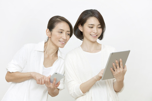 タブレットPCを持つ母親と娘の写真素材 [FYI01321657]